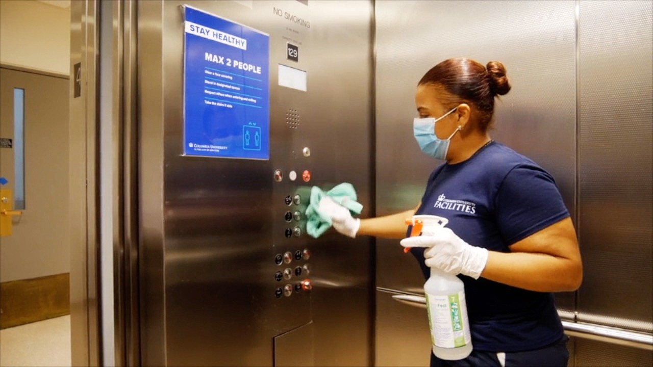 A Facilities and Operations custodial employee cleaning the inside of an elevator with a blue sign stating what the elevator occupancy is.