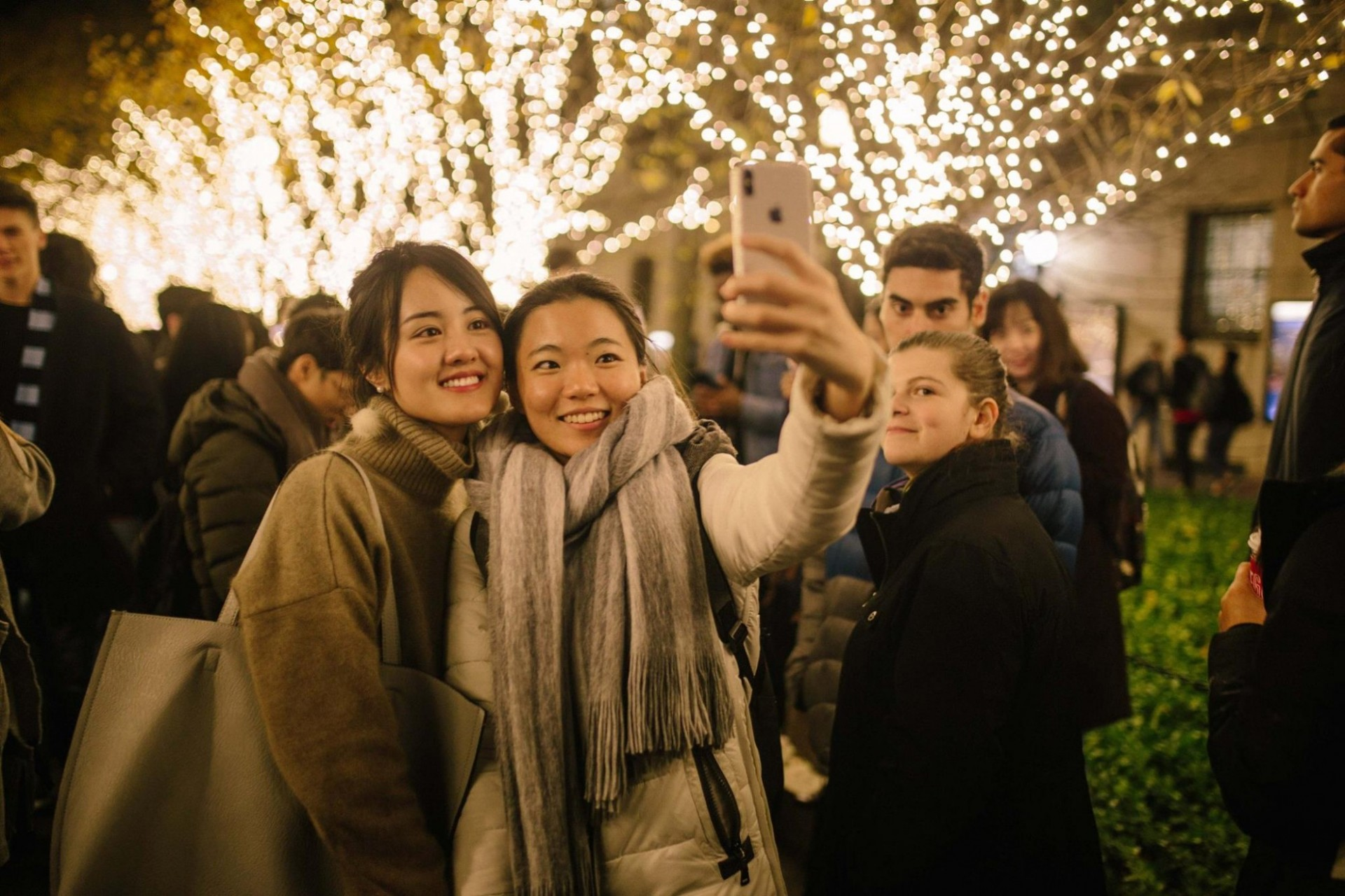 Students take photo in front of lit trees on College Walk
