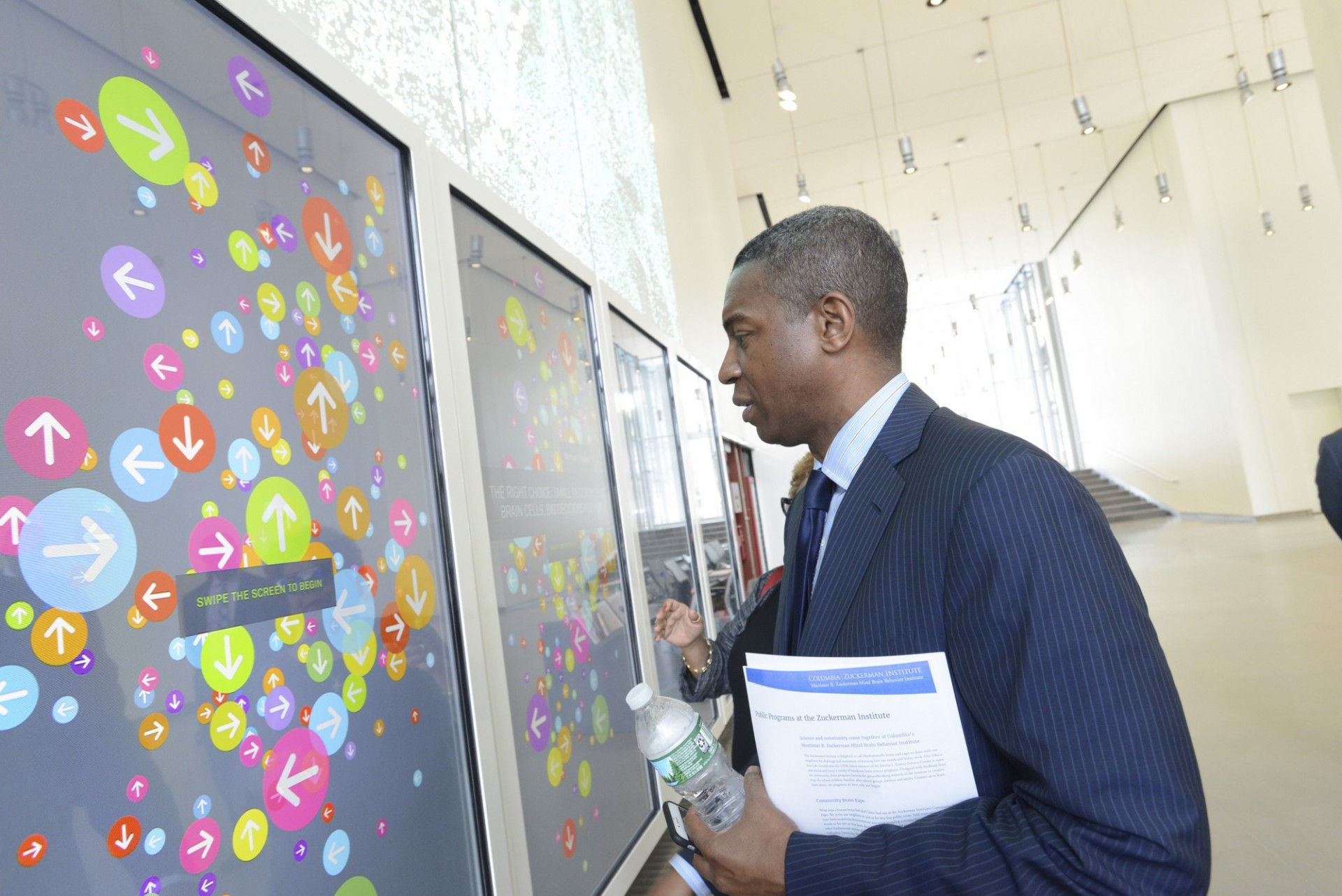 Gerrard Bushell, president and CEO of DASNY, using the Brain Index in the lobby of the Jerome L. Greene Science Center during a recent tour of the building. (Photo credit: DASNY)