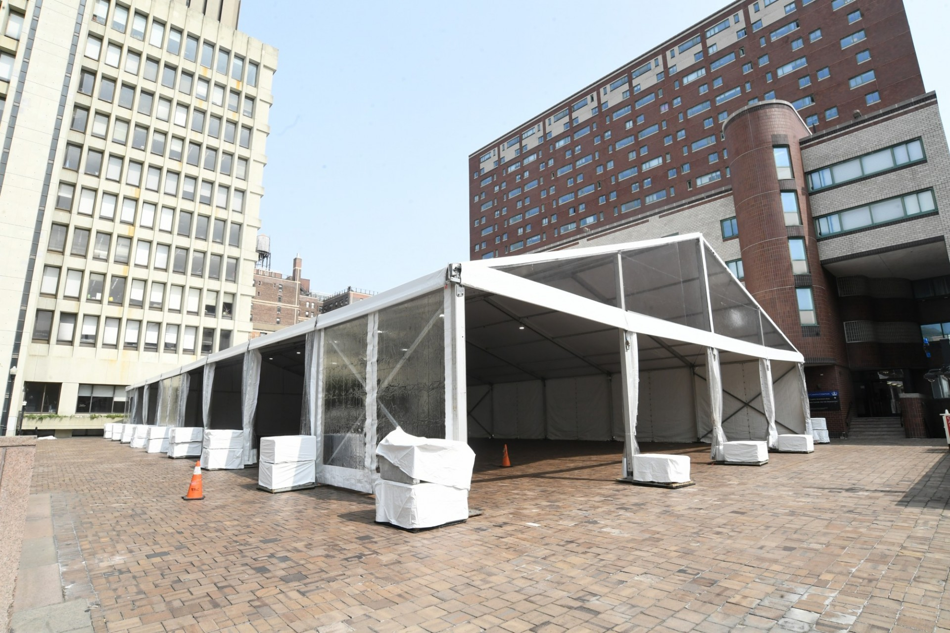 A large white tent is erected on Ancell Plaza between the International Affairs Building and East Campus.