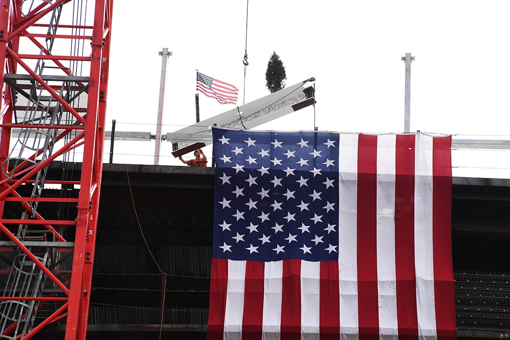 A signed beam with an American flag and fir tree being secured to the Ronald O. Perelman Center for Business Innovation.