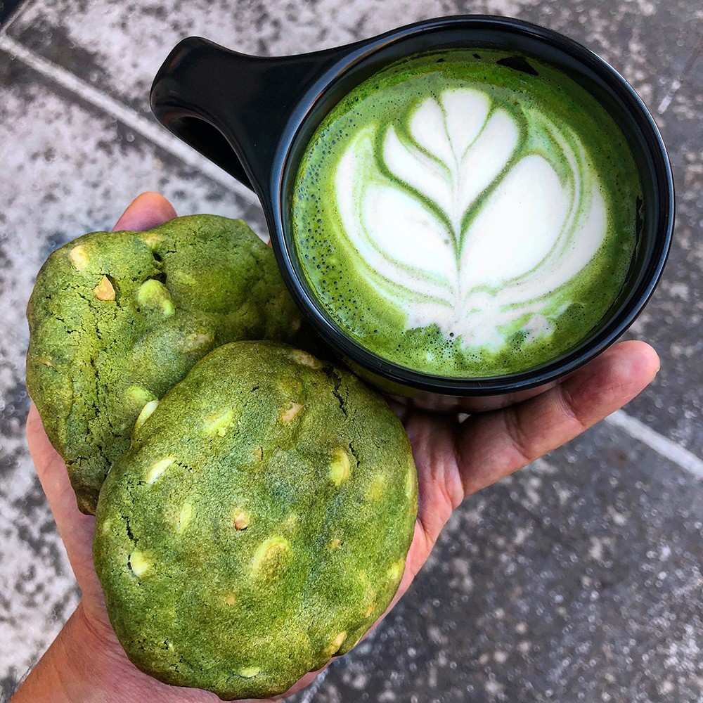 An almond milk matcha latte and two white chocolate almond matcha cookies