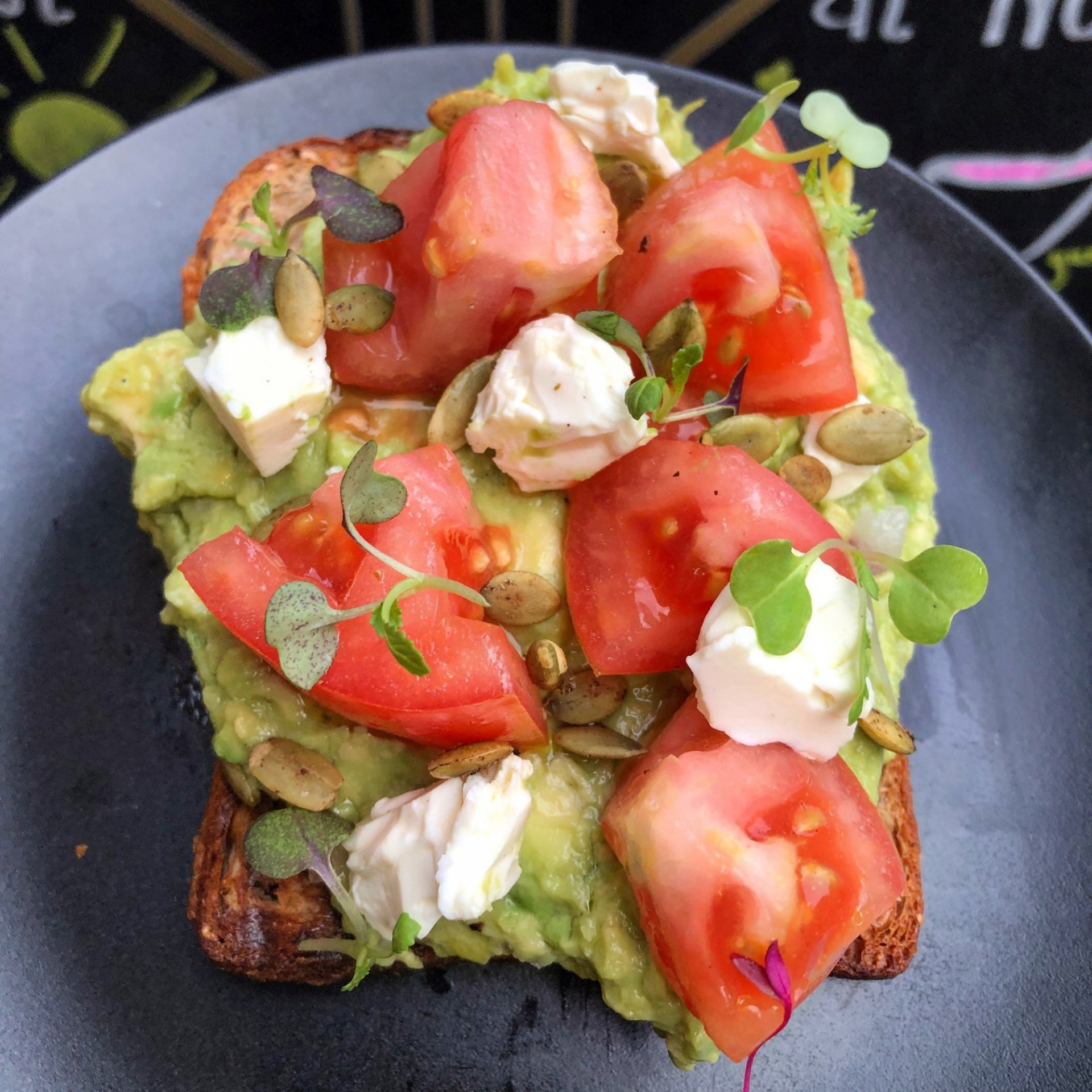Avocado toast with tomatoes, feta cheese, and pepitas