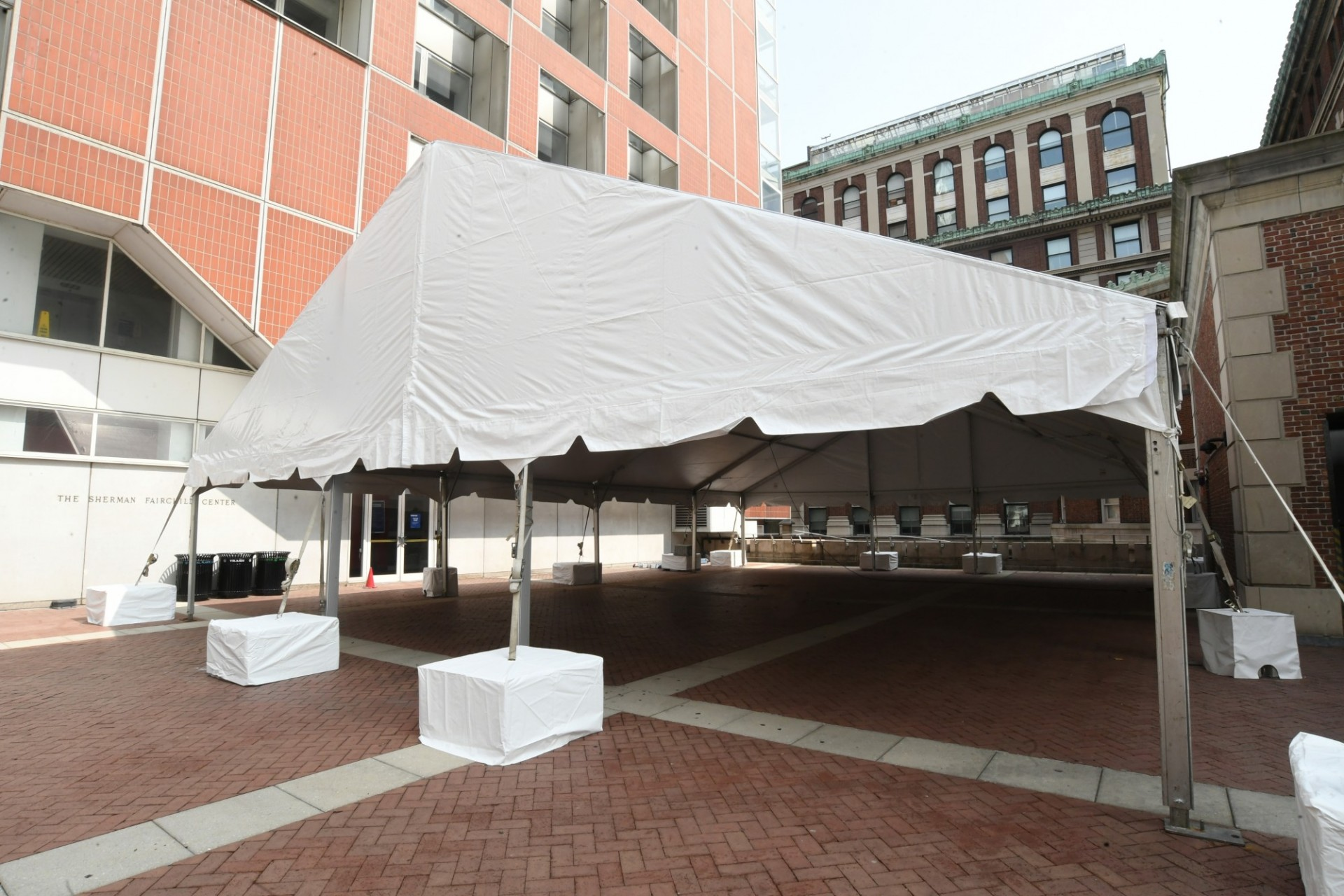 A large white tent is erected next to the Fairchild building.
