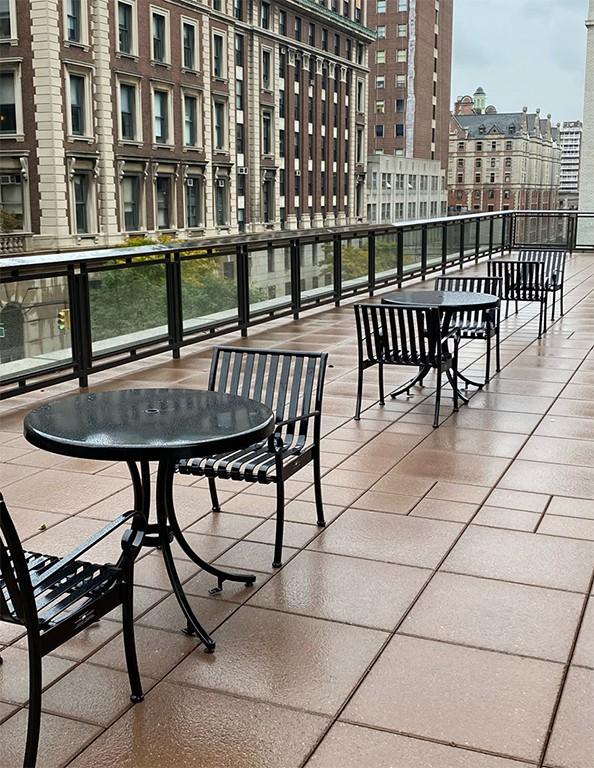 Black cafe tables and chairs line the International Affairs Building terrace.