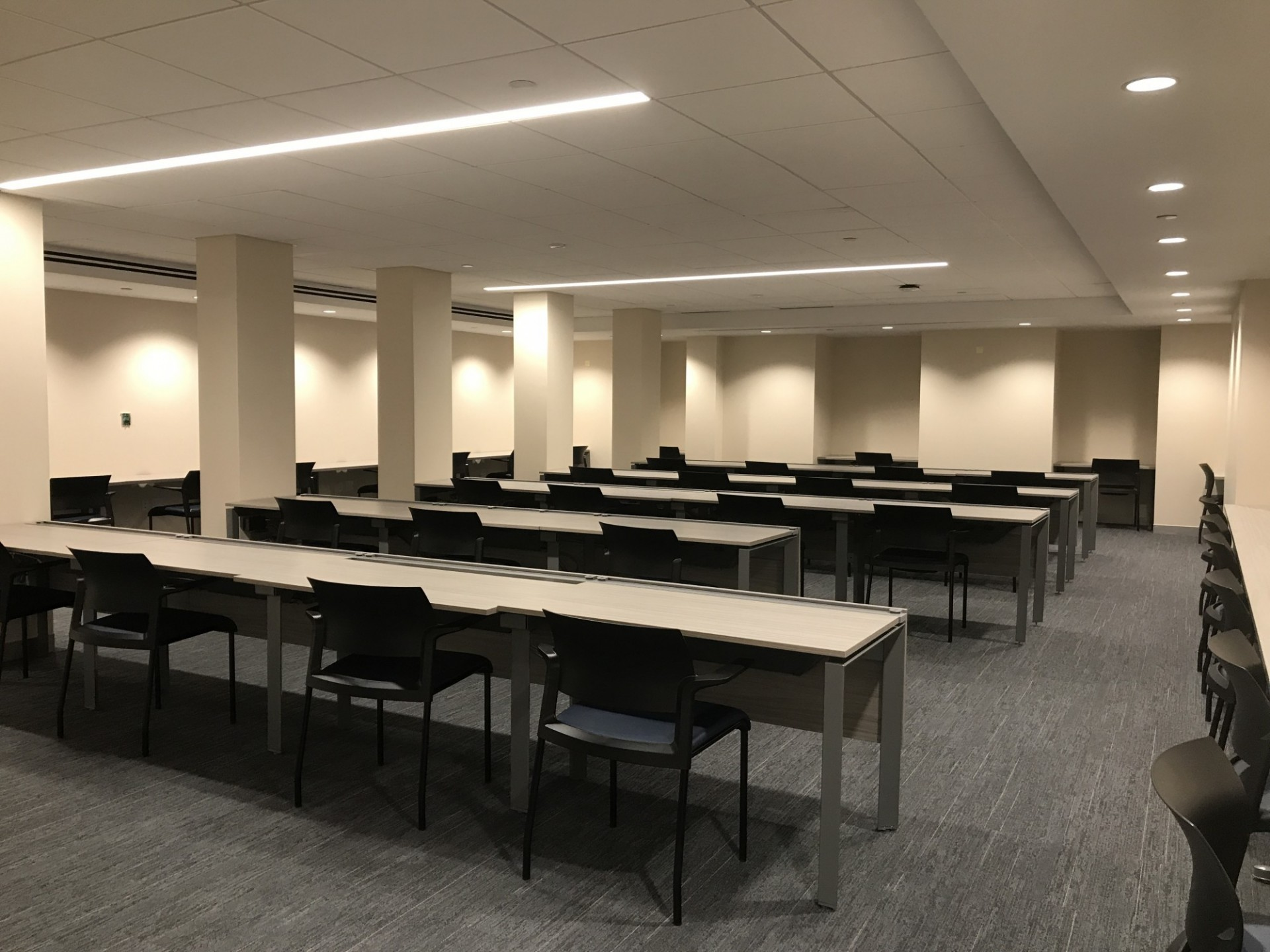 A large testing room in Havemeyer Hall with tables and chairs.
