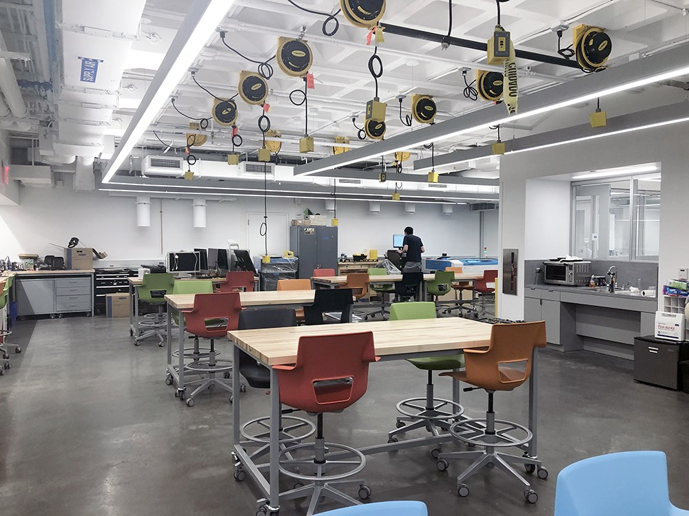 The interior of the new Innovation Foundry with tables, chairs, and research equipment