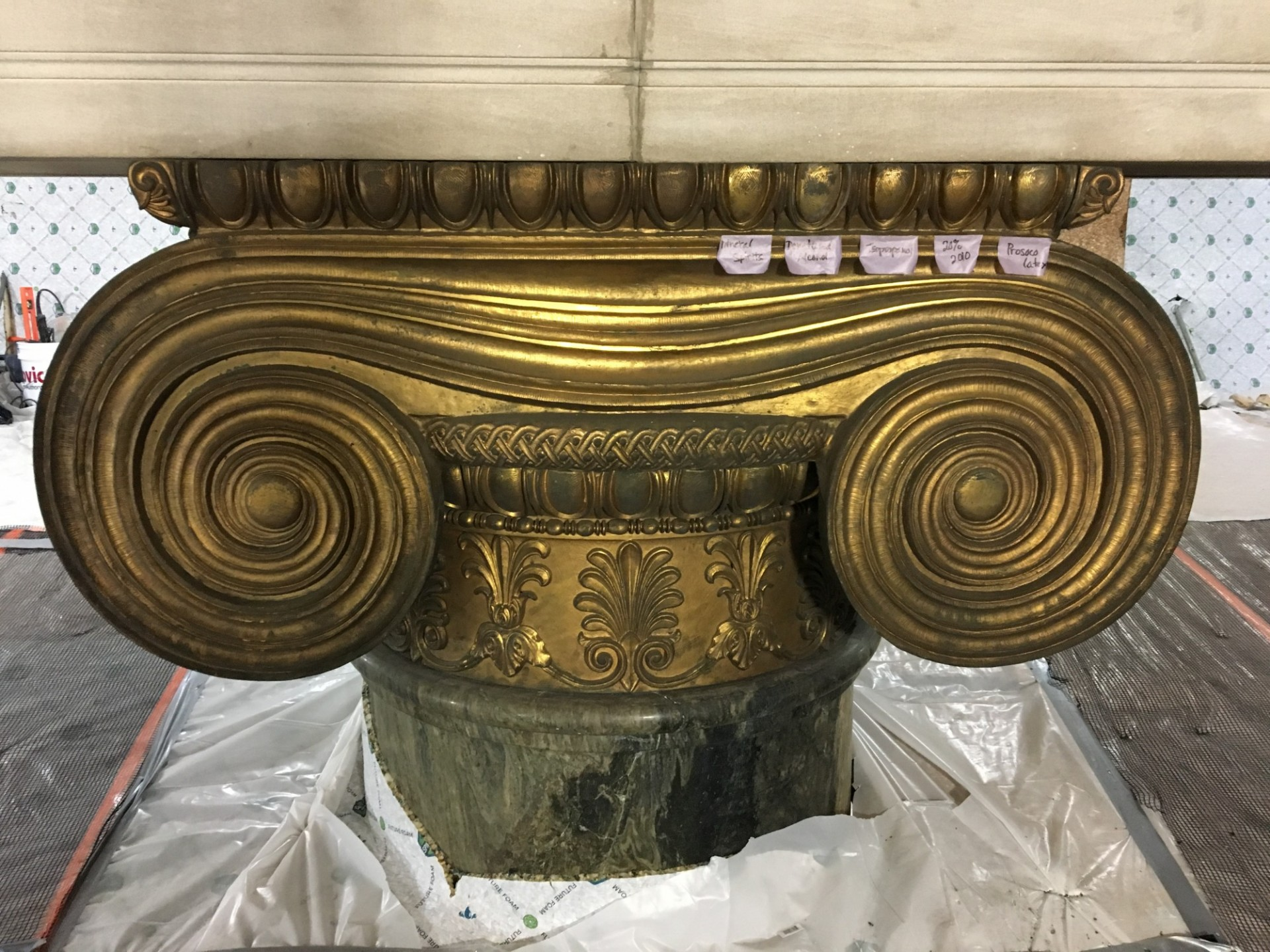 The historic preservation contractor tests multiple cleaning agents at the gilded bronze column capital to determine which one will most effectively restore the intended finish.
