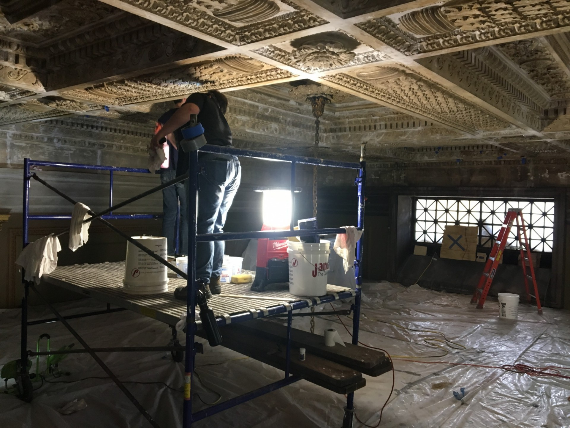 Conservators at work making repairs to the plaster ceiling. Site protection includes elaborate sound barriers with felt-tip panels, padding lining the walls., and plastic covering, collectively designed to minimize noise and protect from dust.