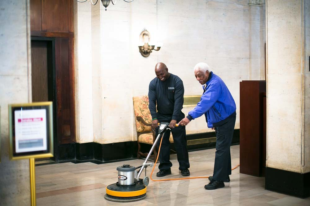 CUFO custodial workers polish the floors in the lobby of University Apartment Housing.