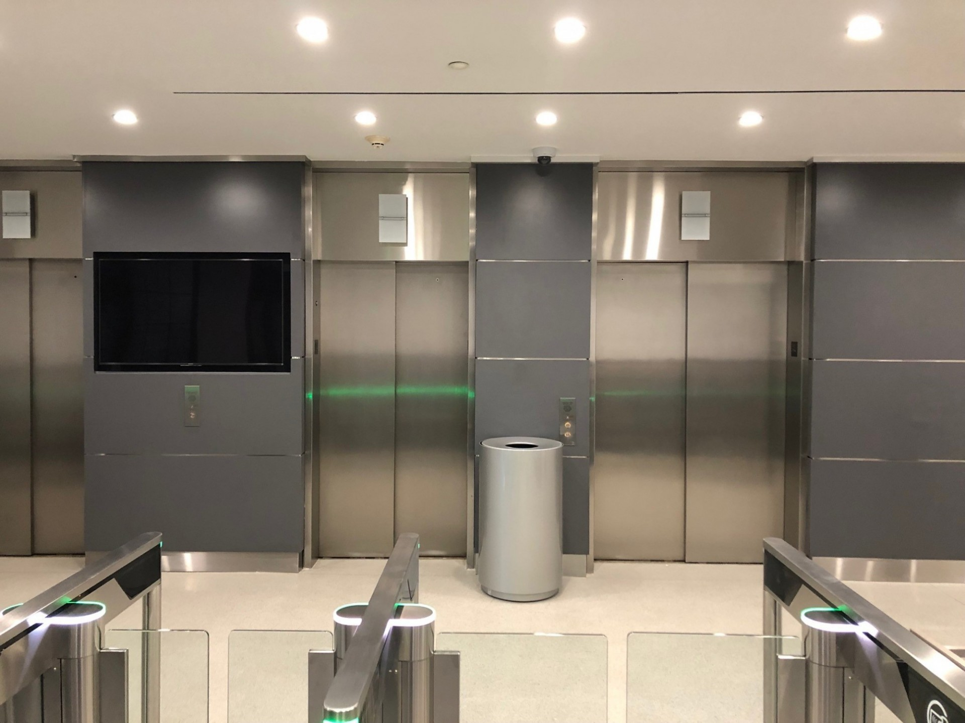 A bank of elevators behind turnstiles