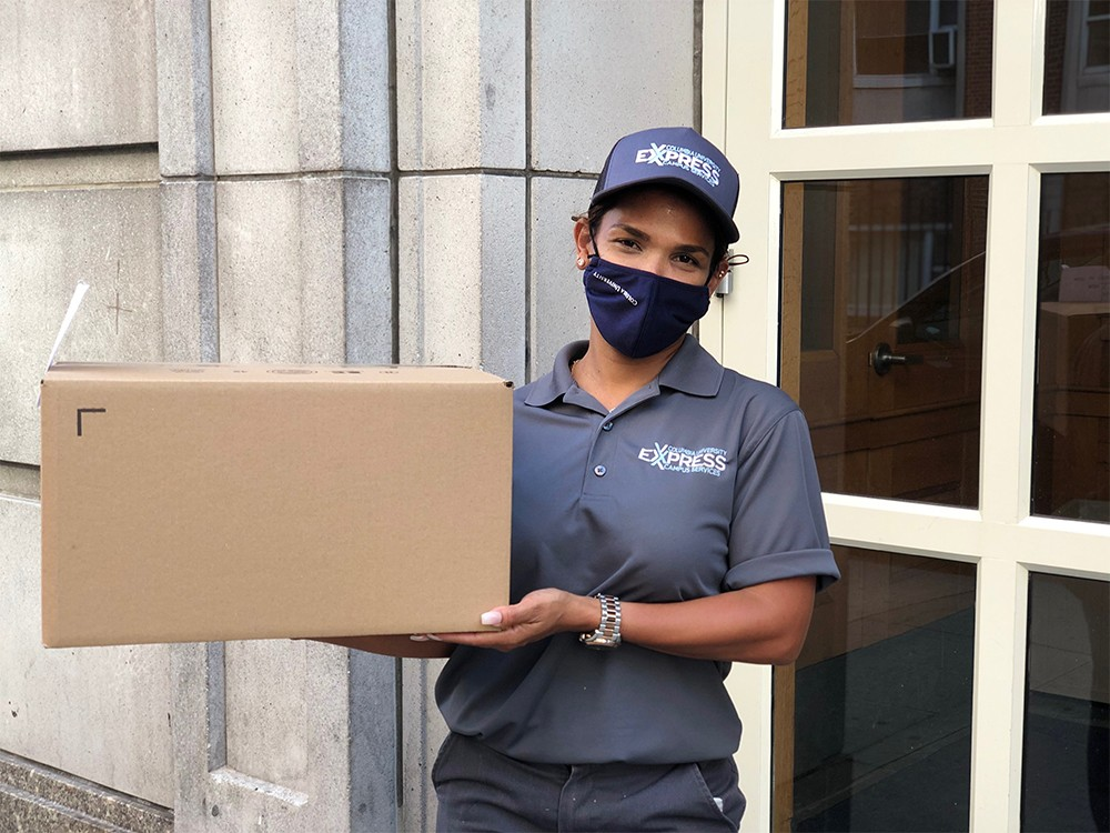 A person with a Campus Services Express uniform delivers a package to a residence hall.