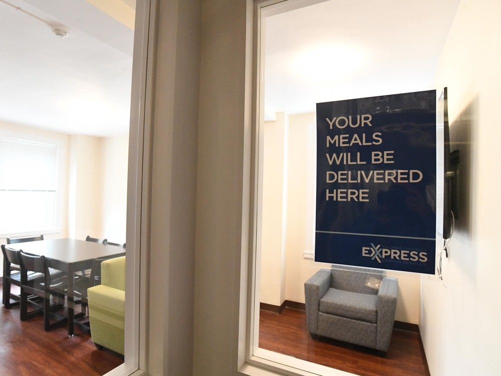 "A sign attached to the window of a student lounge that reads, ""Your meals will be delivered here - Express."""