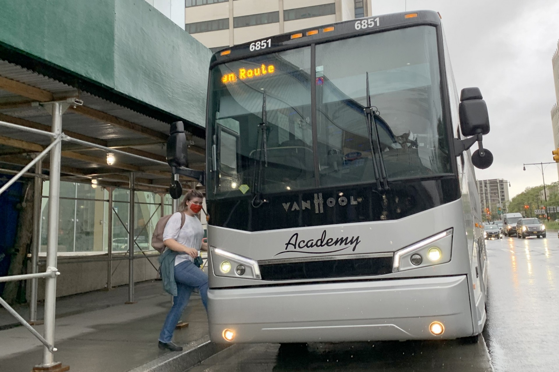 "A person gets on a large gray Academy bus that has ""CU Brooklyn"" written on it from a sidewalk with sidewalk shedding."