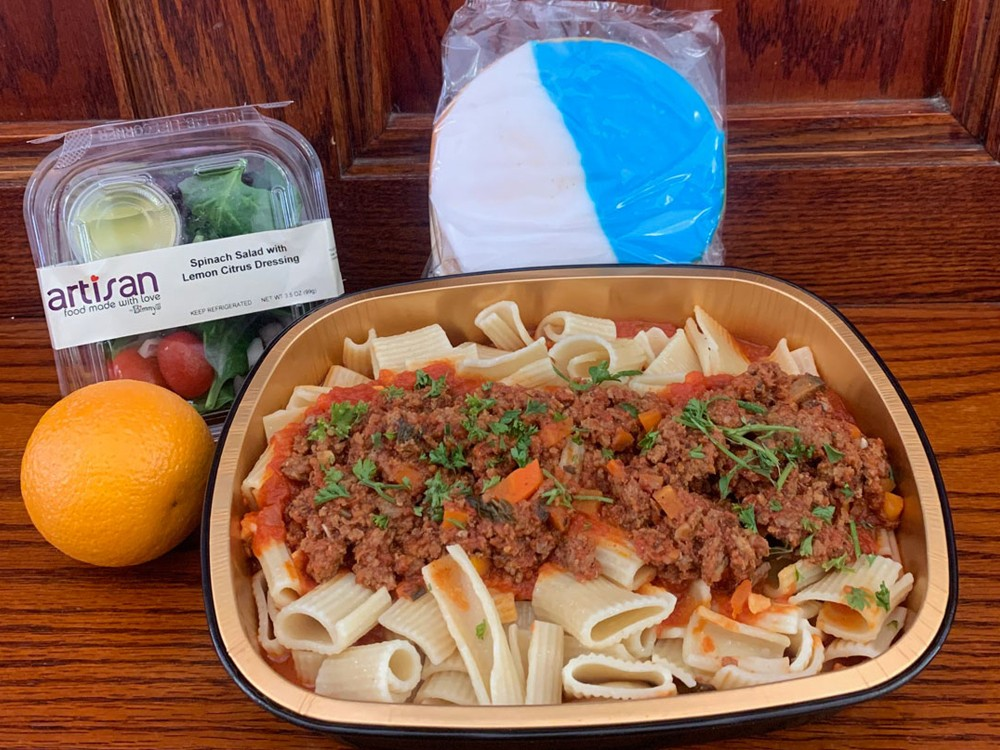 A pasta and meat sauce meal prepared for students during the delivery period, with a salad, orange, and large white and blue cookie.