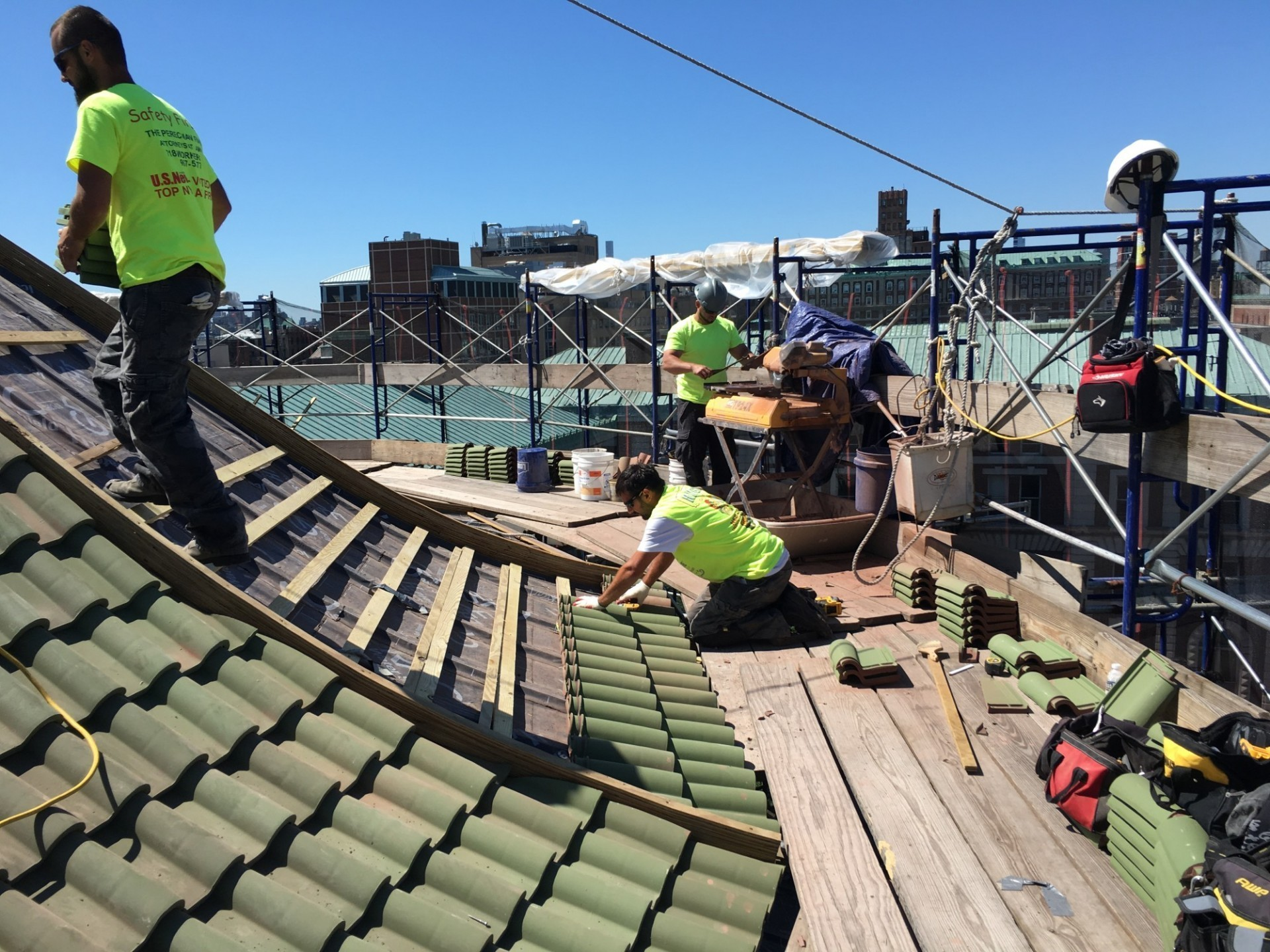 Workers replacing terra cotta roof tiles on top of the Chapel's roof during a cloudless, sunny day.